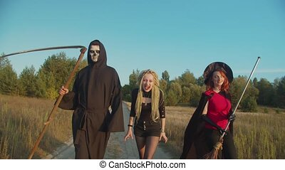 Fiend creatures, scary grim reaper with scythe, bloodthirsty female vampire and black witch with broom plotting evil deeds, walking on rural road at sunset while haunting for souls on halloween.