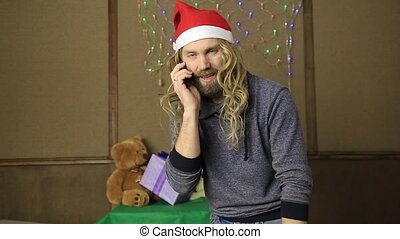 evil dwarf or bad santa talking on a phone and drinking...