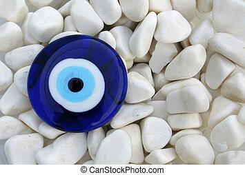 evil eye (amulet) on white peebles