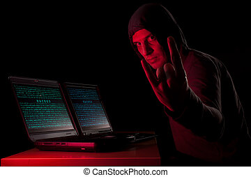 Evil hacker - Hacker in front of two laptops in dark...