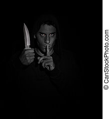 Evil man gesturing silence while holding a knife. Black and...