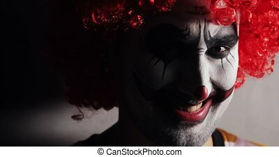 Portrait of jester with terrible makeup and curly red wig hairs. Traditional frightening humor. Evil smile and disgust on face of scary clown man looking at camera in Halloween holiday in dark.