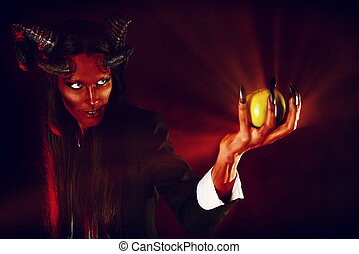 Portrait of a devil with horns holding apple. Devilish temptation. Fantasy. Art project.