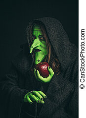 Evil witch with a rotten apple and a spider on her hands
