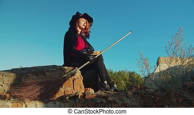 Evil witch with spellbook casting spells at sunset - ...