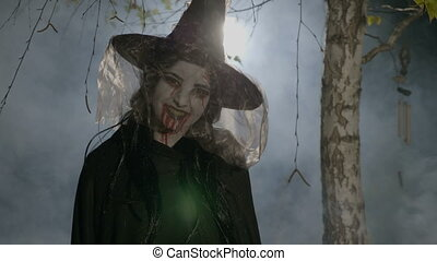 Evil witch zombie with blood on her mouth putting a...