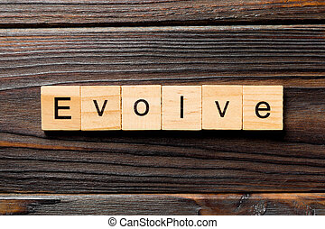 EVOLVE word written on wood block. EVOLVE text on wooden table for your desing, concept