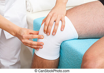 Examination of knee - Doctor examining the twisted knee of...