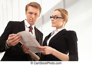 Examining a report. Two confident business people discussing something while looking at the documents