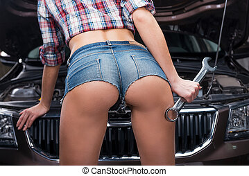 Examining engine. Rear view of beautiful young woman with...