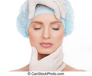 Examining face before plastic surgery. Portrait of beautiful young woman in medical headwear keeping eyes closed while hands in gloves examining her face isolated on white