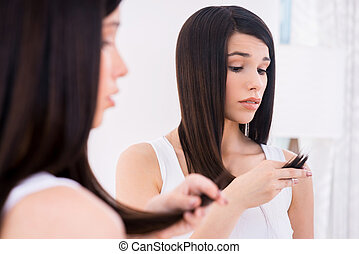 Examining her damaged hair. Frustrated young woman looking at her hair and expressing negativity while standing against mirror