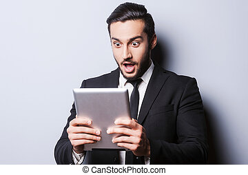 Examining his brand new tablet. Surprised young man in formalwear holding digital tablet while standing against grey background