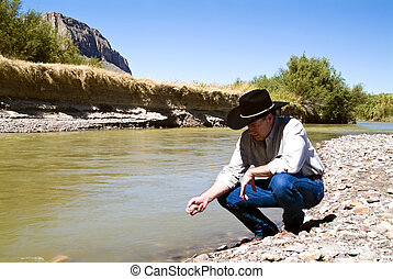 Examining the Terrain - A man dressed in western garb...