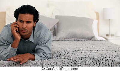 Exasperated man on the phone lying on his bed at home
