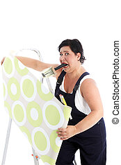 Exasperated woman hanging wallpaper with a brush full of...
