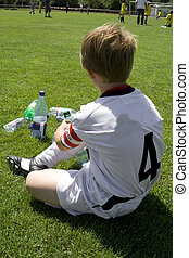 exausted boy takes a rest in the halftime of a football...