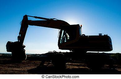 excavadora contraluz, tarde ocaso