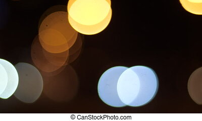 Excavated circles of light flicker against the background of the dark evening city. Flashing glare of yellow, orange and blue light in the dark in the evening. Bright blurry glare of lights blink.