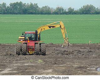 Excavating Machine - large backhoe excavates dirt in field