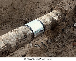 Excavation pit. Old drink water pipe with stainless...