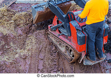 Excavation works at the construction site. Bulldozer or a backhoe loader dumping ground