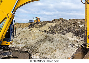 Excavator and bulldozer with caterpillars at building site