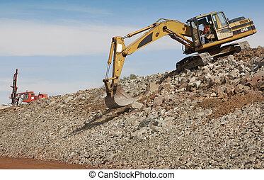 Excavator and drill machine. - Excavator unloading sand at...