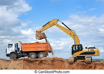 Excavator and rear-end tipper - Excavator loading sand in...