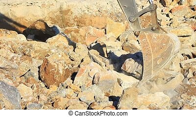 Excavator arm picks up the rocks