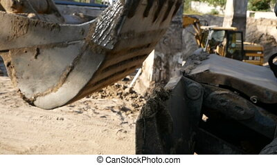 excavator at a construction site drives by camera.