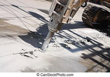 Excavator breaking street asphalt with hydrohammer drill