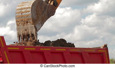 Excavator bucket being dumped into dump truck - Construction...