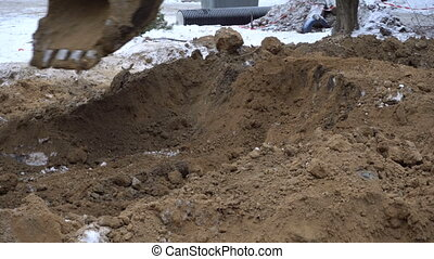 Excavator bucket digs the ground