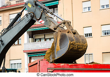 Excavator bucket loading clay in the city
