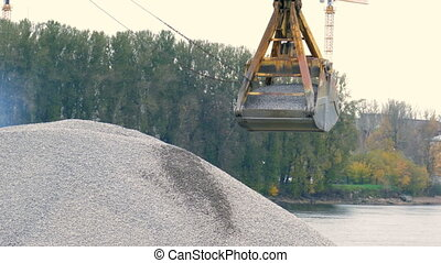 Excavator bucket pours a mountain of rubble on the background of the river