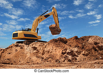 Excavator bulldozer in sandpit with raised bucket over blue ...