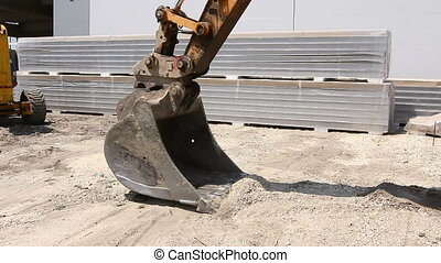 Excavator changes his bucket. - Excavator is replacing tool,...