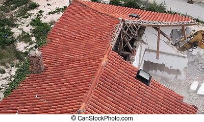 Excavator demolishing house