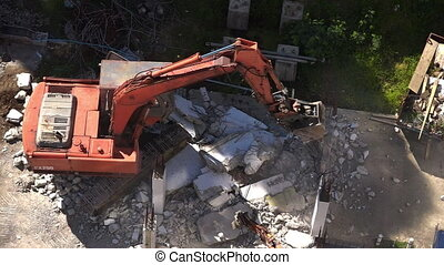 Excavator destroying concrete wall - Aerial birds eye view...