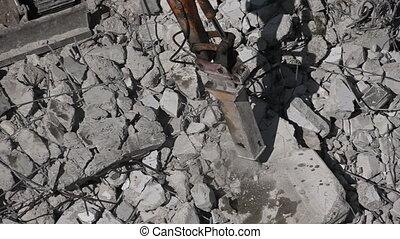 Excavator destroying concrete wall