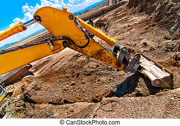 Excavator digging a hole and loading a dumper truck with soil