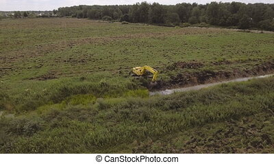 Excavator digging a trench in the field.Aerial video.