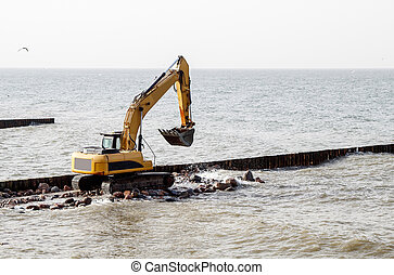 excavator during the construction of a breakwater
