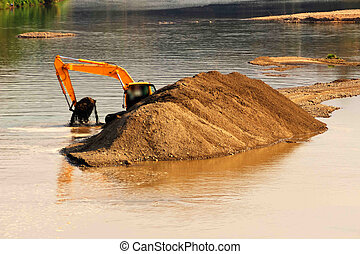 Excavator extracts sand and pebbles from a river in ...
