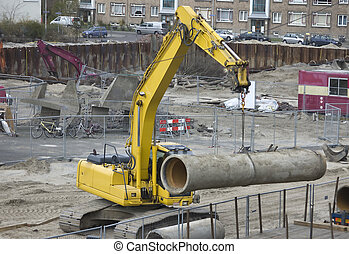 Excavator hoisting sewer pipe - Excavator hoisting a sewer...