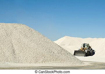 Excavator in a limestone quarry. Piles of limestone rocks