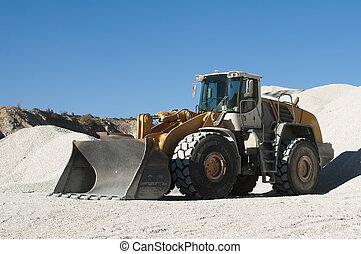Excavator in a limestone quarry.Piles of limestone rocks