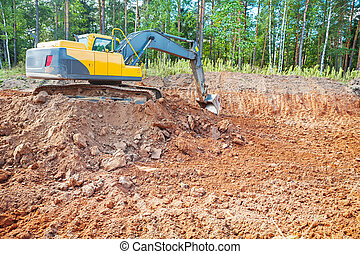 excavator in work on constructon site in forest