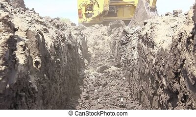Excavator is excavating a ditch - Low angle view on backhoe...